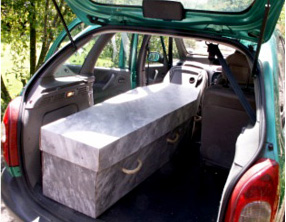 A marbled cardboard coffin in family car